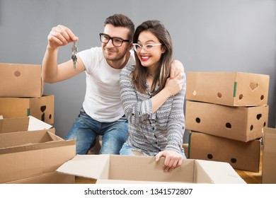 Young and happy married couple moving in new apartment