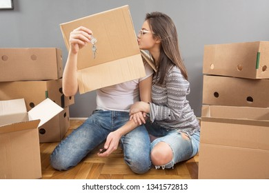 Young and happy married couple moving in new apartment and unpacking boxes