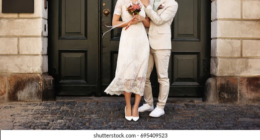 Young and happy married couple walking around. Enjoing their wedding day