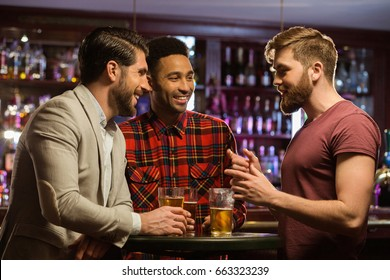 Young happy men drinking beer and talking in cafe or pub