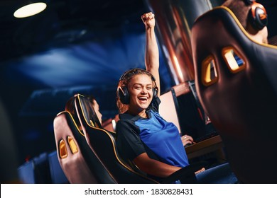 Young happy mixed race girl, female cybersport gamer raising hand up and smiling at camera while participating in eSport tournament