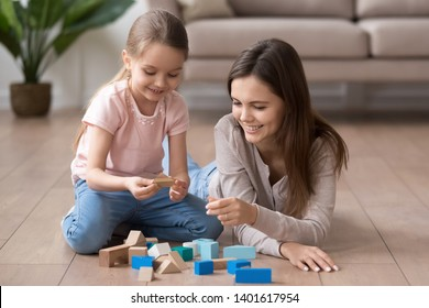 Young happy mom and preschooler daughter sit on floor playing with toy blocks together, smiling mother or nanny and little girl child have fun engaged in funny activity game with building bricks