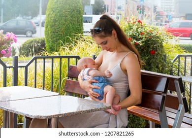 Young happy mother is breastfeeding cute little baby outside at public place, near the busy street with cars on intersection, woman is sitting on the bench at the restaurant terrace and nursing infant
