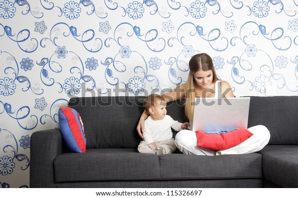 young happy mother and child with laptop at home