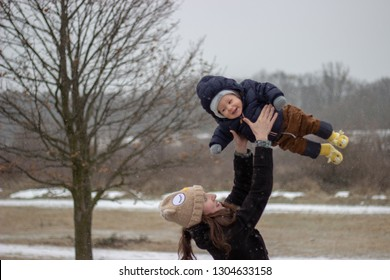 young happy mother is having fun with her very little adorable smiling babyboy son throwing and catching him above her head outside in winter with snowy land in the background