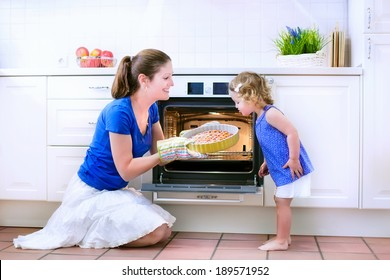 Young happy mother and her adorable curly toddler daughter wearing blue dress baking a pie together in an oven in a white sunny kitchen with modern appliances and devices