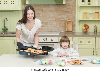 Young happy mother and her child testing cookies