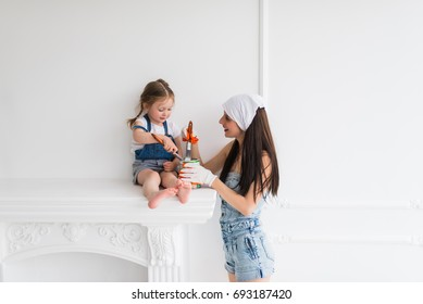 The young happy mother with her daughter do repair at home, they keep brushes in hands and paint