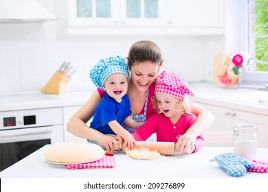 Young happy mother and her kids, adorable toddler girl and a little funny baby boy wearing pink and blue chef hats baking a pie together in a white sunny kitchen with big window