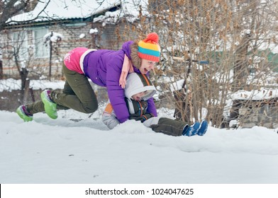 Young happy mother and her little son enjoying winter sledding