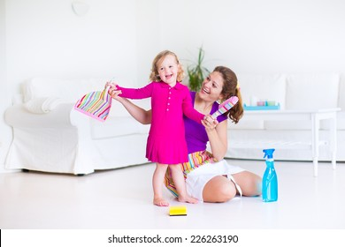 Young happy mother and her little daughter, cute toddler girl, cleaning the house together sweeping the floor in a white sunny living room with modern interior and big white couch