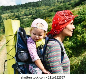 Young happy mother hold little traveller on back - baby girl in carrying backpack enjoying travel adventure, Hiking activity with child on family summer vacation, weekend nature tour.