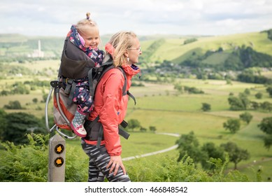 Young happy mother hold little traveller on back - baby girl in carrying backpack enjoying travel adventure, Hiking activity with child on family summer vacation, weekend nature tour