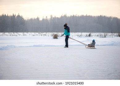 Young happy mother and little baby boy son sledding on snowy winter lake together