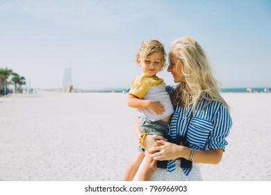 Young happy mother with little blonde son on the beach