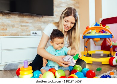 Young and happy mother playing in house with her little son