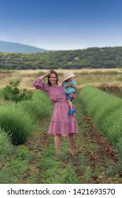 Young happy mother in red dress posing with her boy in a lavender field