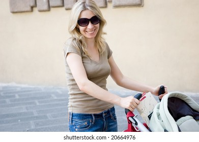 Young happy mother with stroller on street