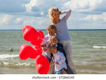 Young happy mother with three boys and red heart balloons at the sea
