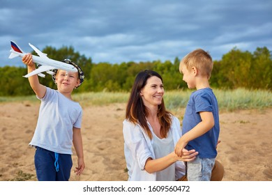 A young happy mother with two boys playing on the sand near the forest, in the hands of one of them a model of a civil aircraft and a hat on his head