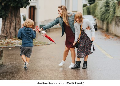 Young happy mother with two kids, little boy and girl, playing outside on a fresh rainy day. Stylish family having fun outdoors