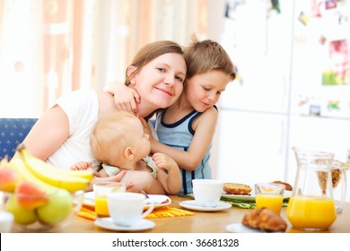 Young happy mother and two kids having breakfast together