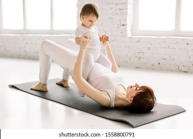 Young happy mother working out, doing butt bridge exercise, wearing white sportswear, little baby girl on her tummy, fitness, postnatal yoga. Healthy lifestyle concept