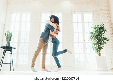 Young and happy multiethnic couple dancing and hugging together in big loft living room in bright apartment