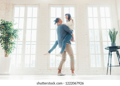 Young and happy multiethnic couple dancing and having fun together in big loft living room in bright apartment