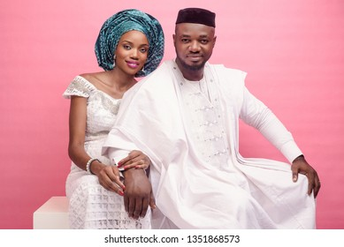 Young happy Nigerian couple in all white traditional native attire and headgear