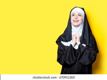 Young happy nun on yellow background