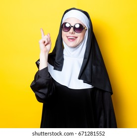 Young happy nun with sunglasses on yellow background
