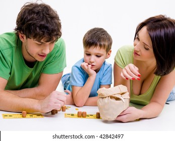 Young happy parents indoors playing with little son