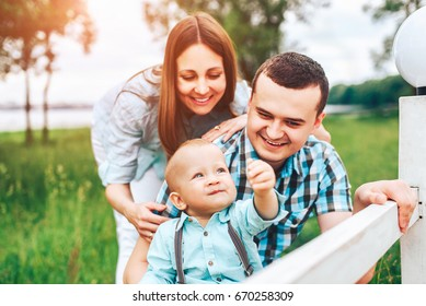 Young happy parents playing with little son outdoor in the park