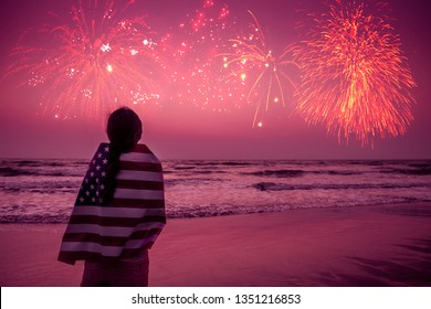 Young happy patriot girl holding the American flag on the 4th of July and looks at the salute in honor of the festival of freedom on sea ocean beach