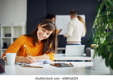 Young happy people discussing business standing at the whiteboard in modern light office, beautiful woman sitting at the table at forefront