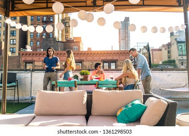 Young happy people having a barbecue dinner on a rooftop in New York - Group of friends having party and having fun