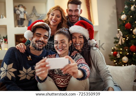 young happy people making christmas selfie の写真素材 今すぐ編集
