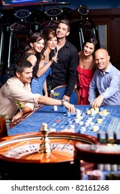 young, happy people playing the casino roulette