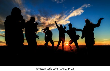 Young happy people silhouettes on the sunset
