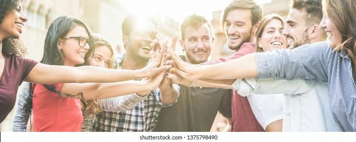 Junge glückliche Menschen, die sich draußen die Hände stapfen - Verschiedene Kulturschüler feiern gemeinsam - Jugendleben, Universität, Beziehung, Humanressourcen, Arbeit und Freundschaft Konzept - Handfokus