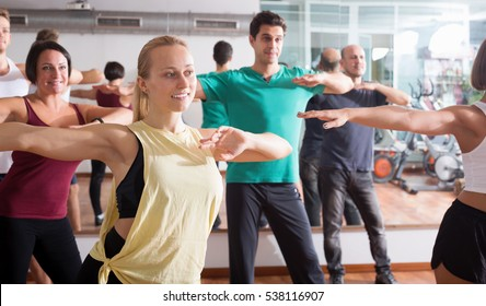 Young happy people studying zumba elements in dancing hall