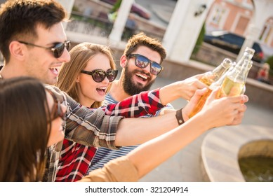 Young happy people walking outdoors. Drinking beverages