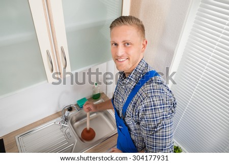 Young Happy Plumber Using Plunger In Kitchen Sink