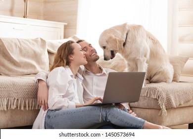 Junge glückliche positive Ehepaare, charmante Frau und junge Mann sitzen alle auf dem Boden neben ihrem geliebten Hund und sehen sich billige Flugtickets für Sommerferien im Internet mit einem Laptop an