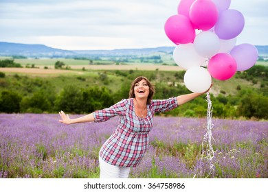 Young happy pregnant woman with balloons outdoors
