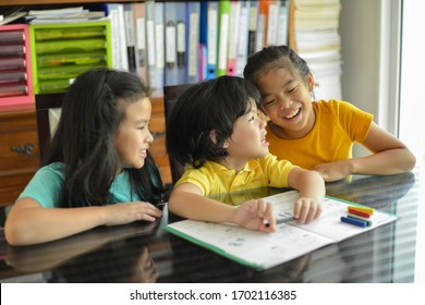 Young happy preschooler laughing with sisters while doing homework on table.Children teaching each other.Asian kids preschooler and elementary students.Young child with sisters learning at home.