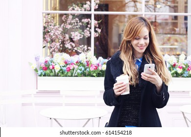 Young happy pretty woman using smart phone holding takeaway coffee on cool cafe with flowers and terrace background. London lifestyle woman in street in front coffee shop with mobile, vacation Europe.