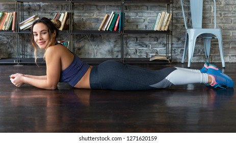 Young happy relaxed fitness woman lying on floor at home