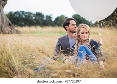 The young happy romantic couple sitting in embrace on the grass outdoor and holding the white balloons in hands